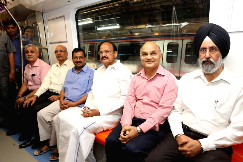 Union Minister for Urban Development, Housing and Urban Poverty Alleviation and Parliamentary Affairs M. Venkaiah Naidu and Delhi Chief Minister Arvind Kejriwal travel in driver-less train ... - Arvind Kejriwal and M. Venkaiah Naidu