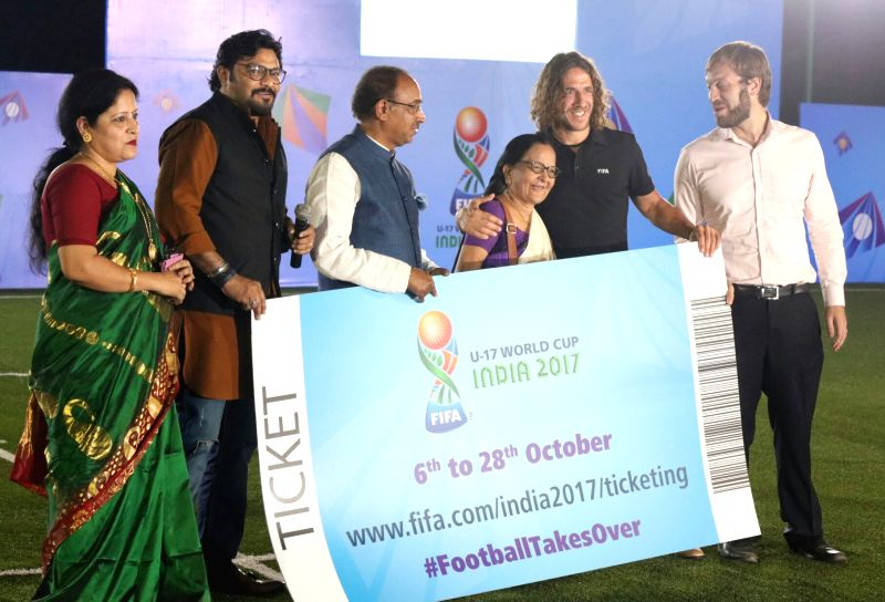 Union Ministers Babul Supriyo and Vijay Goel along with retired Spanish footballer Carles Puyol present the first ticket of the under-17 World Cup to Gauri Bhaduri, grand daughter-in-law ... - Babul Supriyo and Vijay Goel
