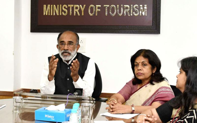 Union MoS Tourism Alphons Kannanthanam addresses after launching the new web portal of Incredible India, in New Delhi on June 14, 2018. Also seen Ministry of Tourism Secretary Rashmi Verma. - Secretary Rashmi Verma