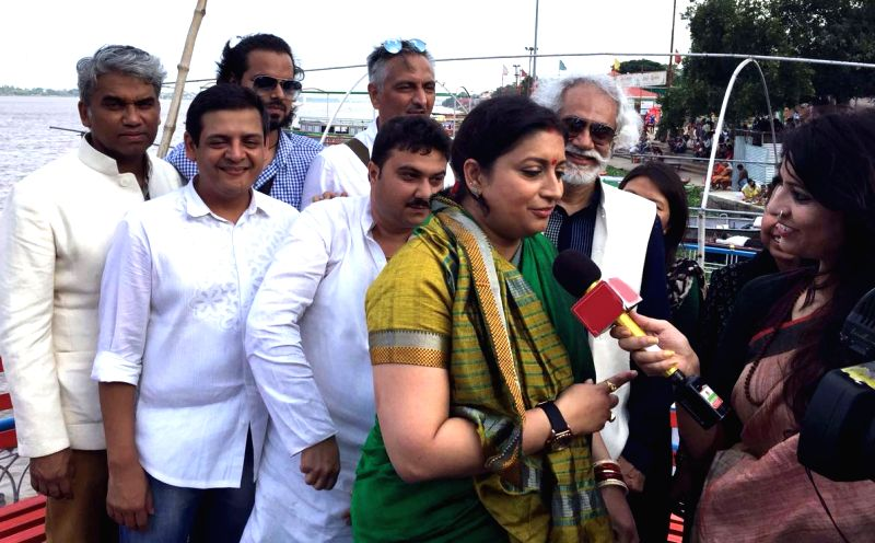 Union Textile Minister Smriti Irani talks to journalist aboard a boat on the Ganga river in Varanasi on Aug 7, 2016. Also seen FDCI President Sunil Seth. - Smriti Irani and Sunil Seth
