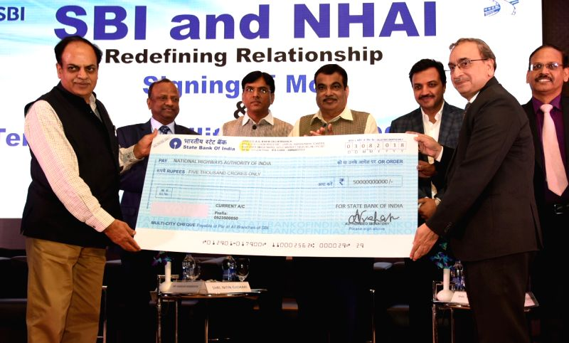 Union Transport Minister Nitin Gadkari, Union MoS Transport Mansukh L. Mandaviya with other dignitaries at the signing ceremony of an MoU between National Highways Authority of India ... - Nitin Gadkari