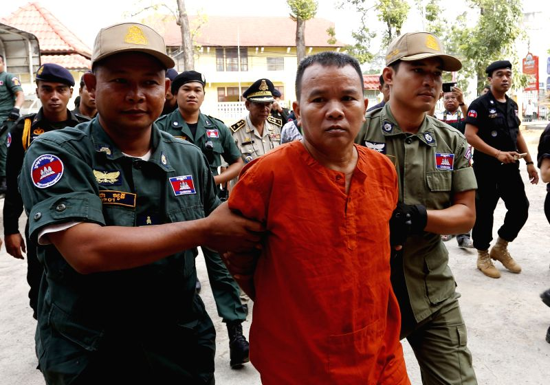 Unlicensed doctor Yem Chrin (C, front) is escorted to the Battambang Provincial Court in Battambang province, Cambodia, Dec. 3, 2015. Yem Chrin, who infected over ...