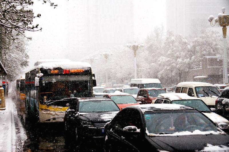 Motorcars move slowly amid snowfall in Urumqi, capital of northwest China's Xinjiang Uygur Autonomous Region, April 23, 2014. A snowfall hit the city on April 23 ...