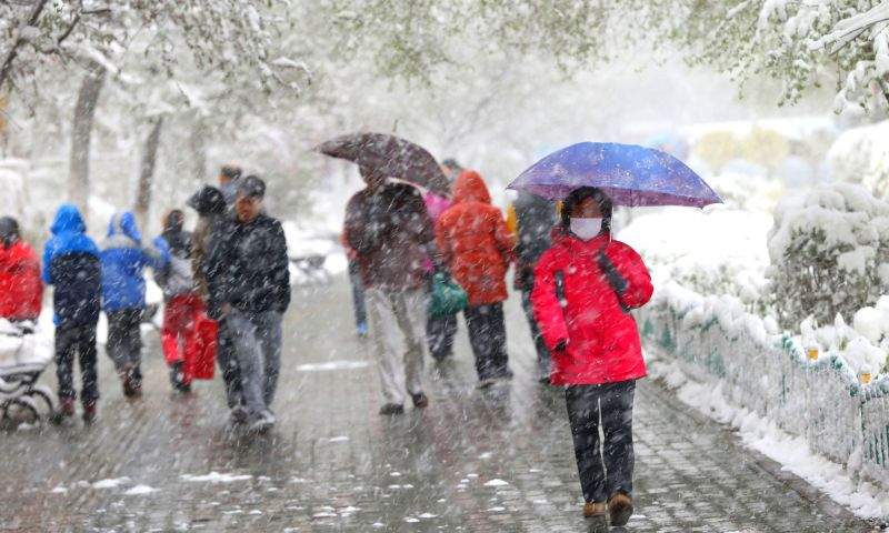 Pedestrians walk in snow in Urumqi, capital of northwest China's Xinjiang Uygur Autonomous Region, April 23, 2014. A snowfall hit the city on Wednesday and the local