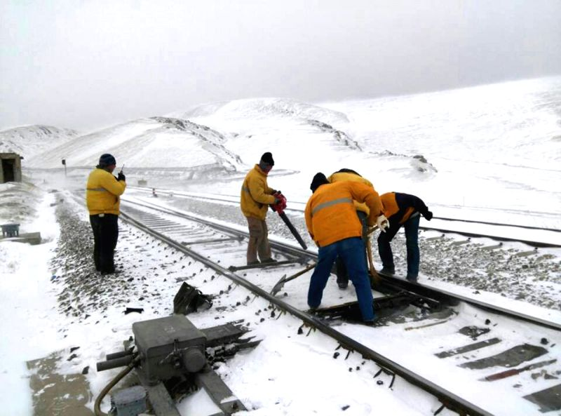 Photo taken with a cell phone shows workers cleaning snow on the railway tracks at a railway station in Hejing, northwest China's Uygur Autonomous Region, April 23,