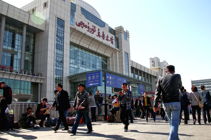 Passengers walk outside the Urumqi South Railway Station in Urumqi, capital of northwest China's Xinjiang Uygur Autonomous Region, May 1, 2014. The order of the ...