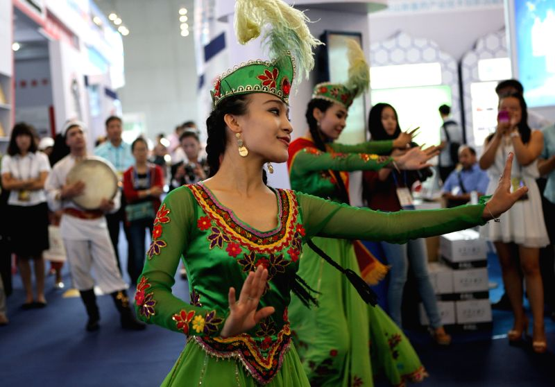 Performers dance during the fourth China-Eurasia Expo (CEE) in Urumqi, capital of northwest China's Xinjiang Uygur Autonomous Region, Sept. 3, 2014.