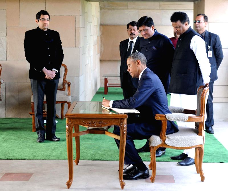 US President Barack Obama signs the visitors book at Rajghat, in New Delhi, on Jan 25, 2015.
