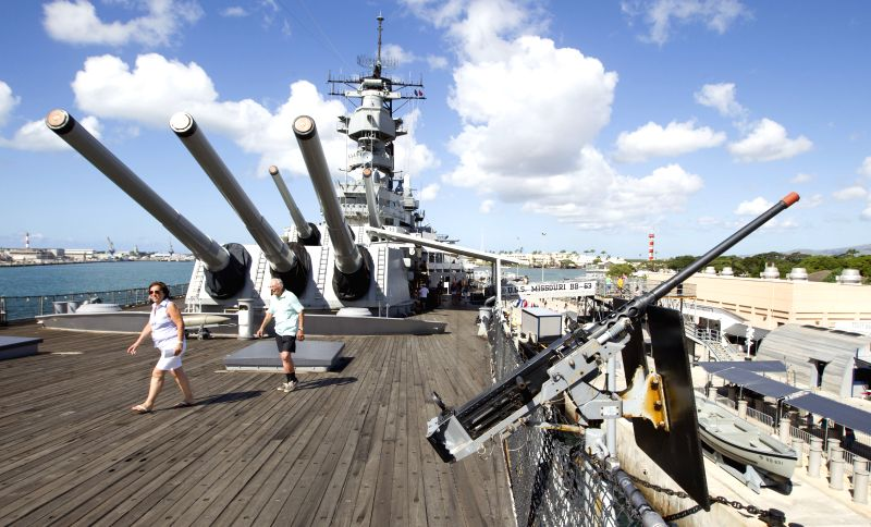 Tourists walk on the deck of the USS Missouri battleship in Pearl Harbor, Hawaii, the United States, July 31, 2014. Japan and the U.S. signed surrender ...