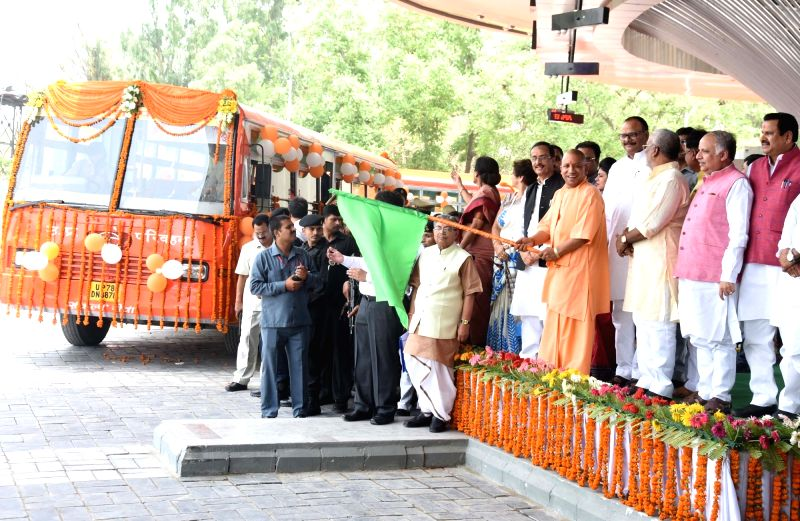 Uttar Pradesh Chief Minister Yogi Adityanath flags off a bus to the Swami Narayan temple in Ayodhya during the inauguration of first-of-its-kind, hi-tech Rs 232 crore Alambagh Bus Terminal, ... - Yogi Adityanath and Dinesh Sharma