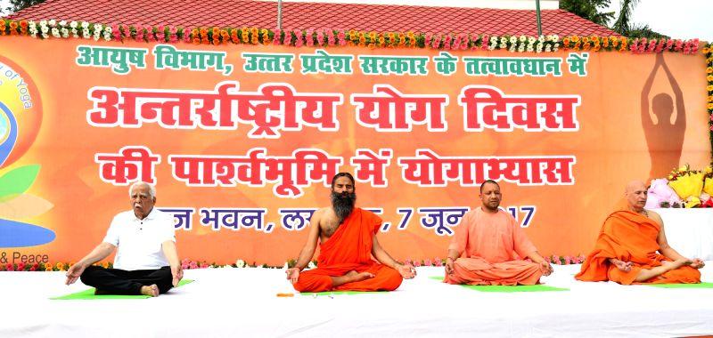 Uttar Pradesh Governor Ram Naik, Chief Minister Yogi Adityanath, Yoga guru Ramdev and Swami Bharat Bhushan practice yoga during the curtain raiser event for International Day of Yoga 2017 in ... - Yogi Adityanath