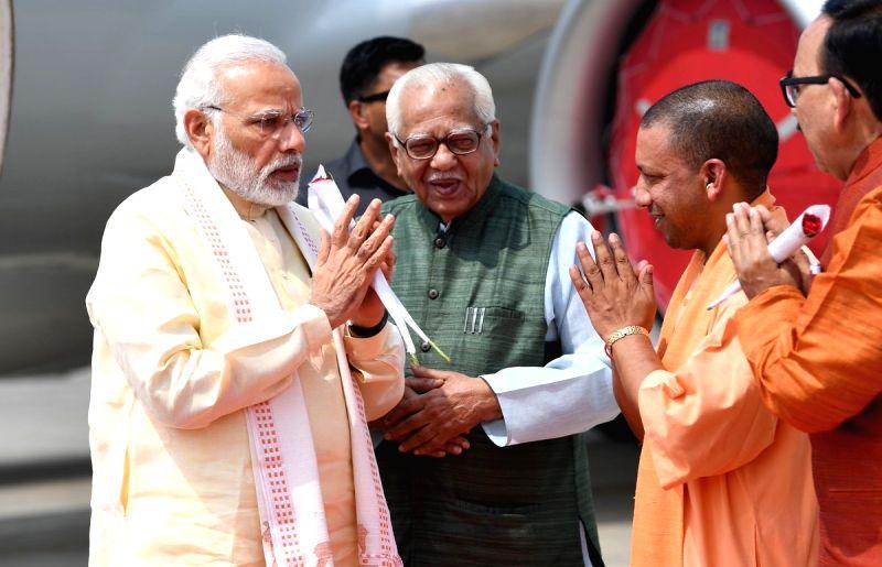 Uttar Pradesh Governor Ram Naik, Chief Minister Yogi Adityanath and state BJP chief Mahendra Nath Pandey receive Prime Minister Narendra Modi on his arrival in Varanasi on July 14, 2018. - Yogi Adityanath, Narendra Modi and Mahendra Nath Pandey