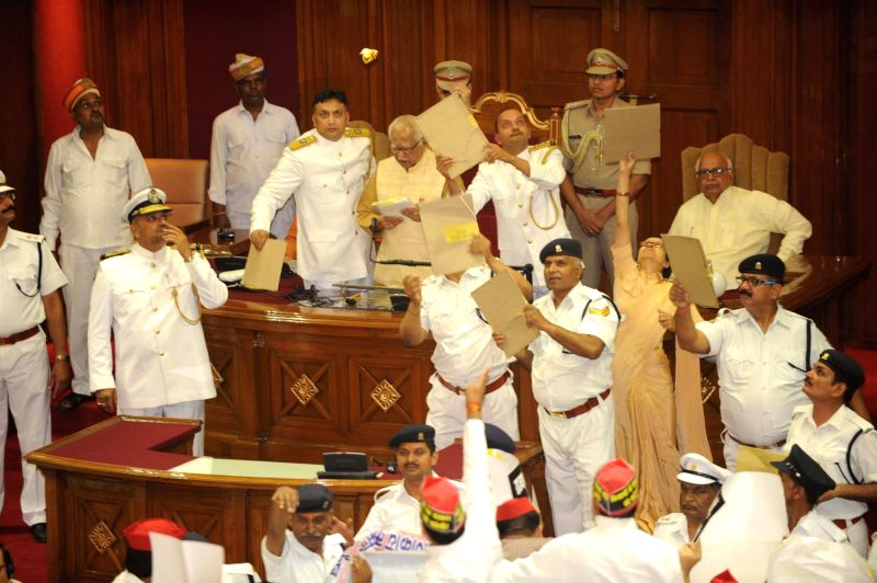Uttar Pradesh Governor Ram Naik's security personnel shield him from the paper missiles being ​hurled at him from the opposition during the first sitting of the 17th Uttar Pradesh Assembly in ...