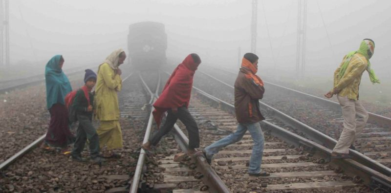 Uttar Pradesh: People risk their lives as they cross an unmanned railway crossing on a foggy day in Uttar Pradesh.