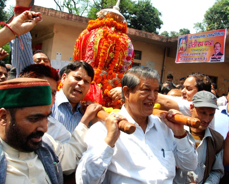 Uttarakhand Chief Minister Harish Rawat carries the doli of Vishwanath Jagdishila during a procession in Dehradun on May 17, 2014. - Harish Rawat
