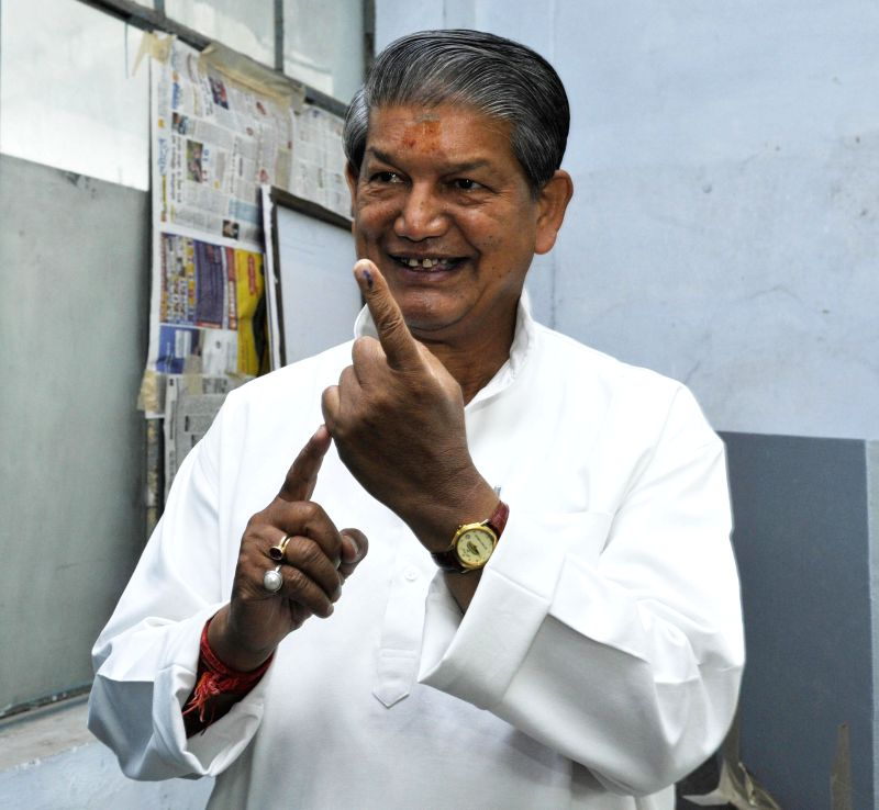 Uttarakhand Chief Minister Harish Rawat shows his fore finger marked with phosphorous ink after casting his vote at a polling booth during the eighth phase of 2014 Lok Sabha Polls in Dehradun on May .