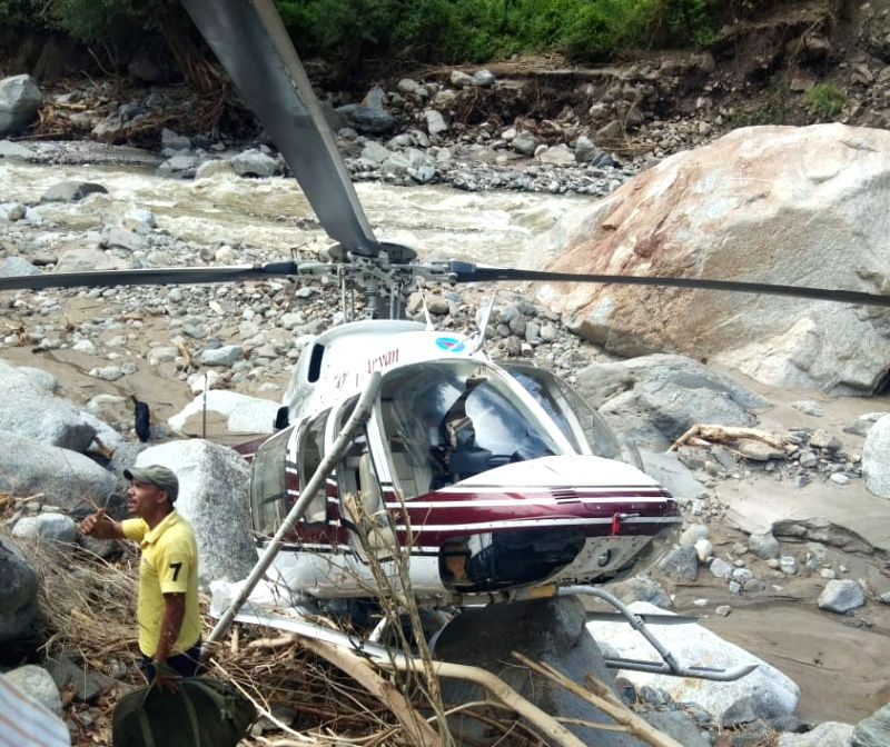 Uttarkashi: The Private helicopter carrying relief material to flood-affected areas that made an emergency landing near the Tikochi river in Uttarkashi district of Uttarakhand, on Aug 23, 2019. Pilot of the helicopter escaped with minor injuries. The