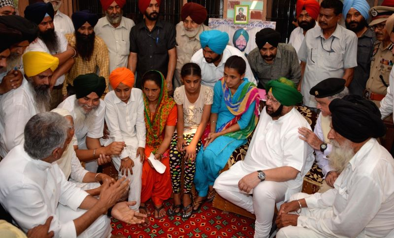 Vain Poin: Punjab Chief Minister Captain Amarinder Singh meets the bereaved family of martyr Paramjit Singh at village Vain Poin, some 40 km away from Amritsar on May 7, 2017. - Captain Amarinder Singh and Paramjit Singh