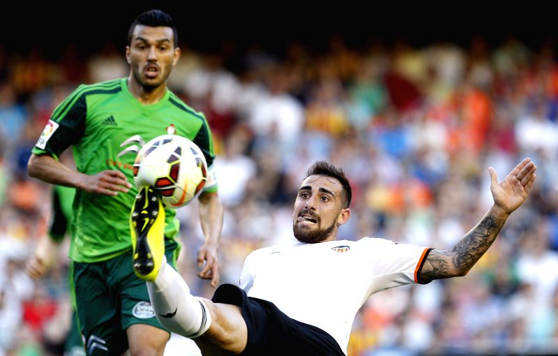 :Valencia CF's striker Paco Alcacer (R) duels for the ball with Celta's Gustavo Cabral (L) during the Spanish Liga Primera Division soccer match played at Mestalla stadium, in Valencia, ...