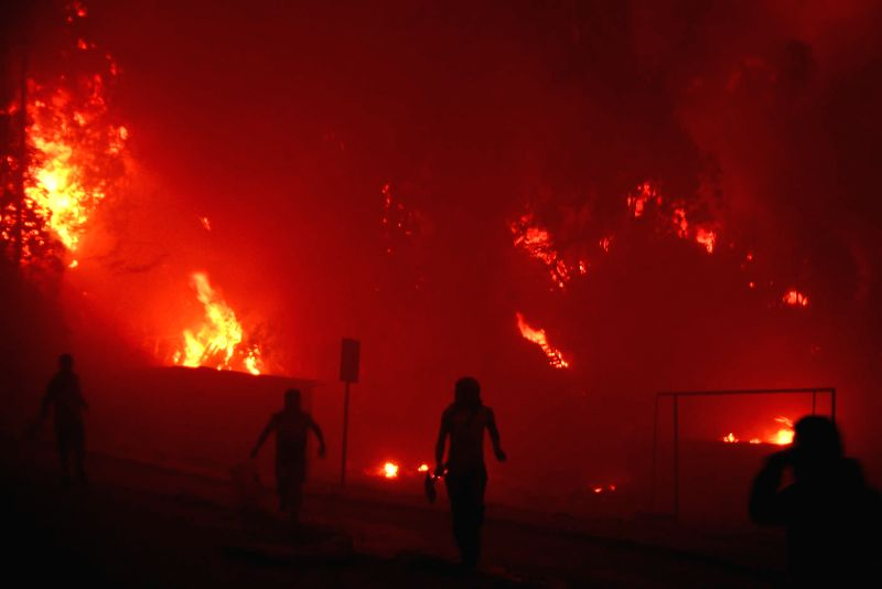 People evacuate from the zone affected by a fire in Valparaiso, Chile, on April 12, 2014. More than 100 homes were burned due to the forest fire, local ...