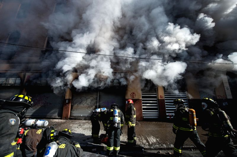 VALPARAISO, May 21, 2016 - Firefighters try to extinguish a fire during a march called by the Confederation of Chilean Students (CONFECH), in Santiago, capital of Chile, on May 21, 2016. ...