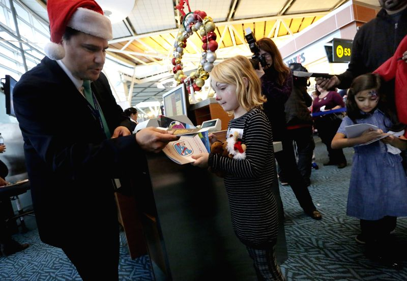 An airline staff helps a sick kid check in during the North Pole visit event at Vancouver International Airport in Vancouver, Canada, Dec. 10, 2014. About 100 sick kids are invited to go ..