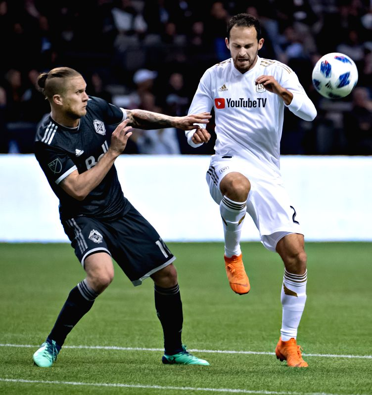 VANCOUVER, April 14, 2018 - Vancouver Whitecaps' Marcel de Jong (L) vies with Los Angeles FC's Marco Urena during the Major League Soccer (MLS) regular season soccer match between Vancouver Whitecaps ...