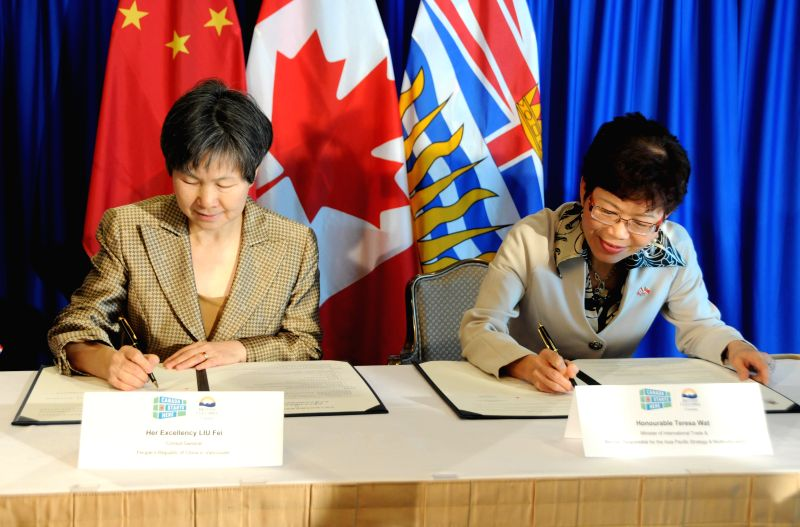 Liu Fei (L), Chinese consul-general in Vancouver, and Teresa Wat, British Columbia minister of international trade, sign an agreement to boost mutual trade and ..