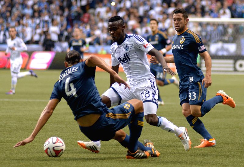 Vancouver Whitecaps' Gershon Koffie (C) vies with LA Galaxy's Omar Gonzalez (L) during their MLS soccer match at BC Place in Vancouver, Canada, on April 19, ...