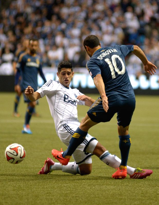 Vancouver Whitecaps' Matias Laba (L) vies with LA Galaxy's Landon Donovan during their MLS soccer match at BC Place in Vancouver, Canada, on April 19, 2014. The .