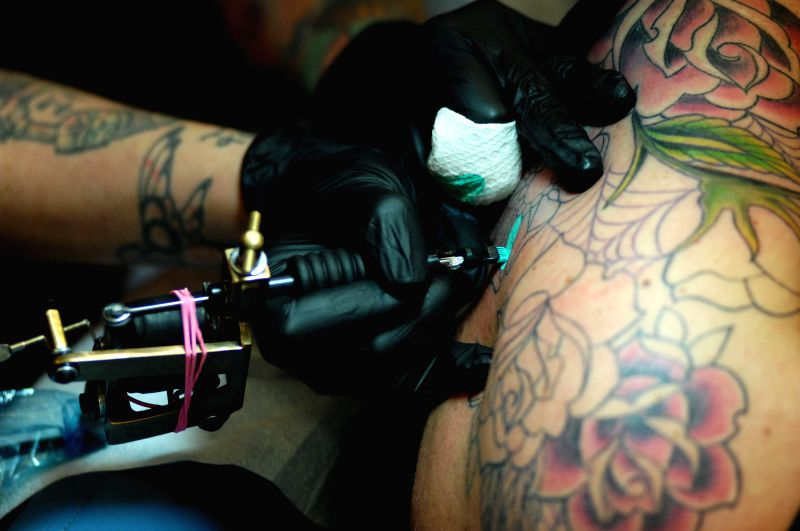 An tattoo artist makes tattoo for a customer at the 2014 Vancouver Tattoo and Culture Show in Vancouver, Canada, April 25, 2014. The weekend event drew together .