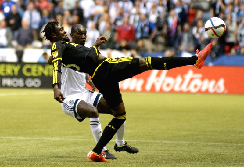 Columbus Crew's Kei Kamara (front) battles with Vancouver Whitecaps' Pa-Modou Kah  during their MLS soccer game at BC Place in Vancouver, Canada, April 8, 2015. Vancouver ...