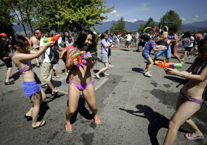 People shoot each other with water pistols during the water fight at the Stanley Park in Vancouver, Canada, Aug. 9, 2014. About 500 people gathered for the 8th ...