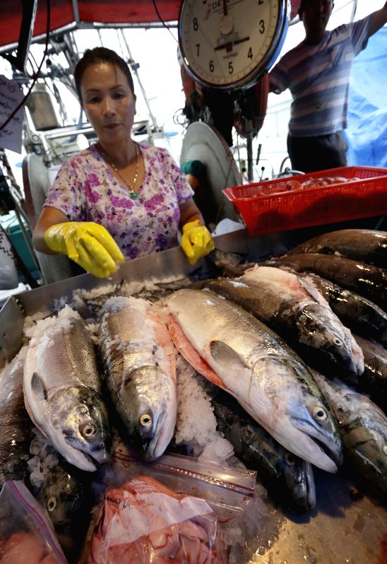 A woman prepares sockeye for sale at the dock of Steveston Village in Richmond, Canada, Aug. 12, 2014. At the first week of the official opening to commercial ...