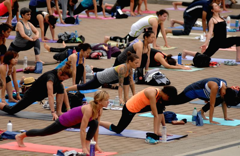 People take part in the 2014 Yogathon in Vancouver, Canada, Aug. 16, 2014. Participants from 46 cities around the world gathered here to join the 2014 Yogathon to