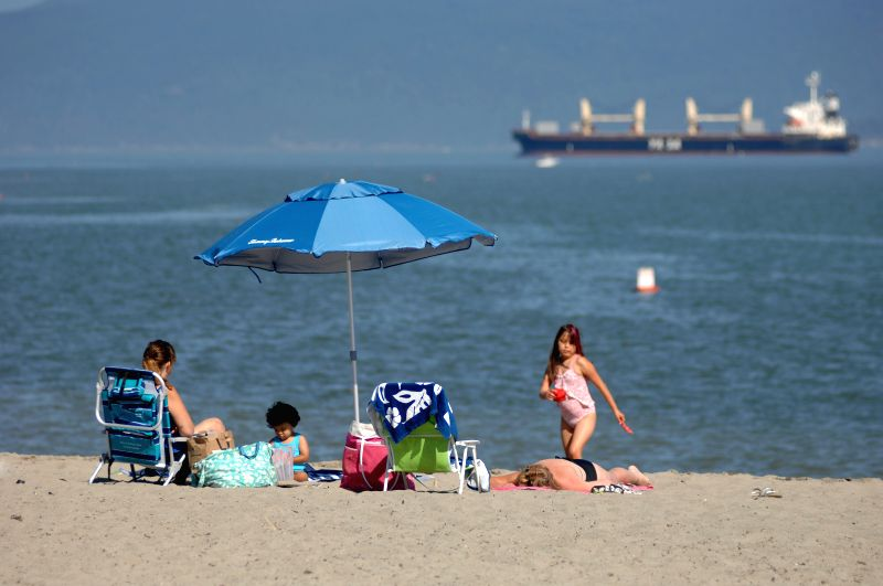 A family enjoy their time at the Jericho beach in Vancouver, Canada, Aug. 19, 2014. Influential British magazine The Economist named Vancouver as one of the ...