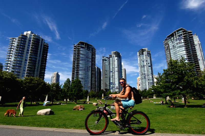 A man rides a bicycle in the Yaletown area in Vancouver, Canada, Aug. 19, 2014. Influential British magazine The Economist named Vancouver as one of the world's ..