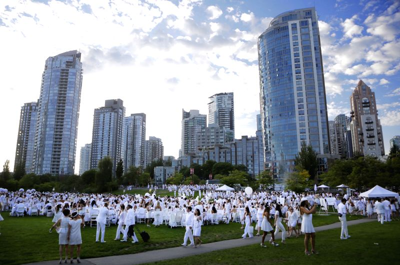 "Local residents participate in the ""Diner en Blanc"" (Dinner in White) event at David Lam Park  in Vancouver, Canada, Aug. 21, 2014. About 3,500 people .."
