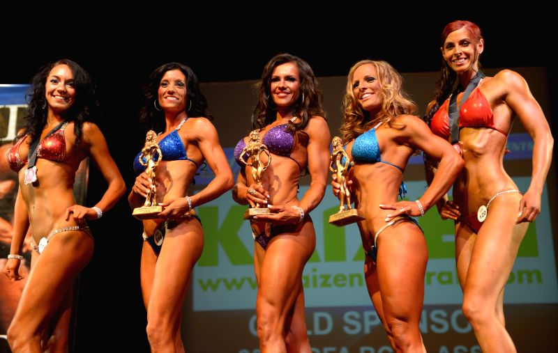 Female athletes pose with their trophies during the 2014 International Drug Free Athletics (IDFA) BC Classic Bodybuilding competition in North Vancouver, BC, ...