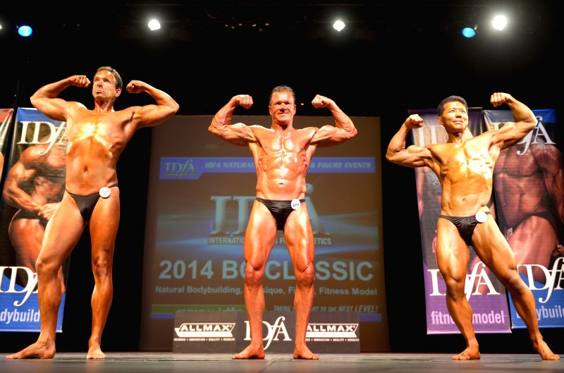 Male athletes compete during the 2014 International Drug Free Athletics (IDFA) BC Classic Bodybuilding competition in North Vancouver, BC, Canada, Aug. 23, 2014. .