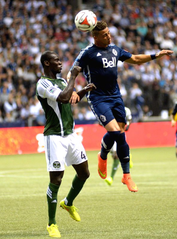 Vancouver Whitecaps' Erik Hurtado (R) vies with Portland Timbers' Pa Modou Kah during their MLS soccer game at BC Place in Vancouver, Canada, on Aug. 30, 2014. ...
