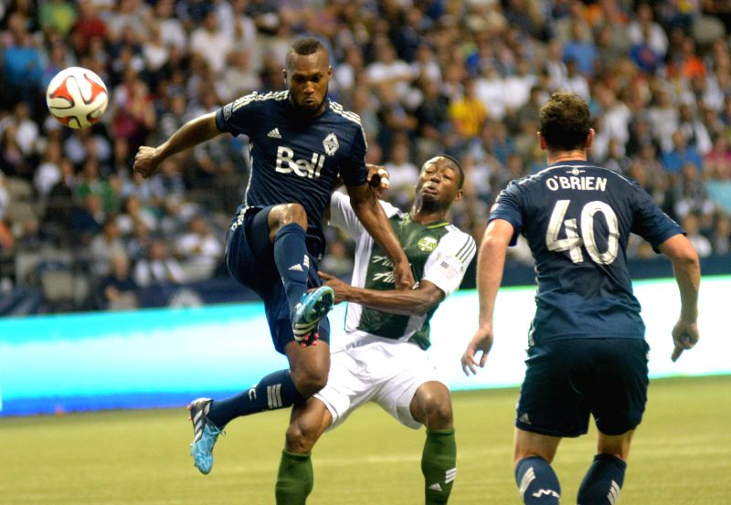 Vancouver Whitecaps' Kendall Watson (L) vies with Portland Timbers' Fanendo Adi (C) during their MLS soccer game at BC Place in Vancouver, Canada, on Aug. 30, ...