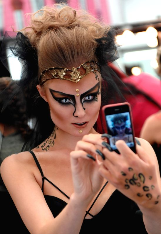 A model takes a selfie of her make-up during the 2014 International Make-Up Artist Trade Show (IMATS) in Vancouver, Canada, Aug. 9, 2014.