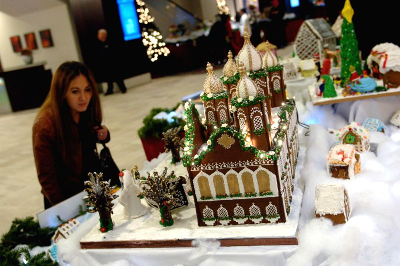 Vancouver (Canada): A visitor looks at gingerbread houses and their characters displayed at Hyatt Regency Hotel in Vancouver, Canada, on Dec. 5, 2014