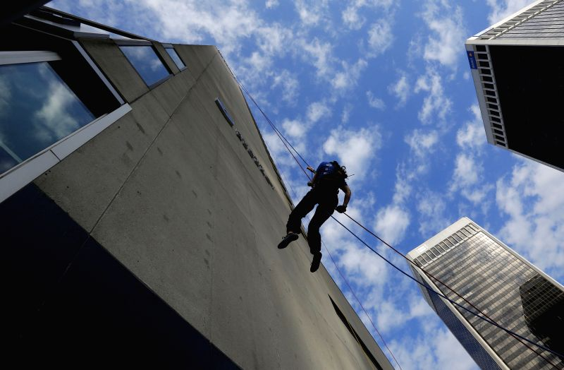 VANCOUVER (CANADA), July 23, 2014 A participant rappels down the edge of the building at Hyatt Regency Hotel in Vancouver, Canada, July 22, 2014. The Rope for Hope is a challenge event ...