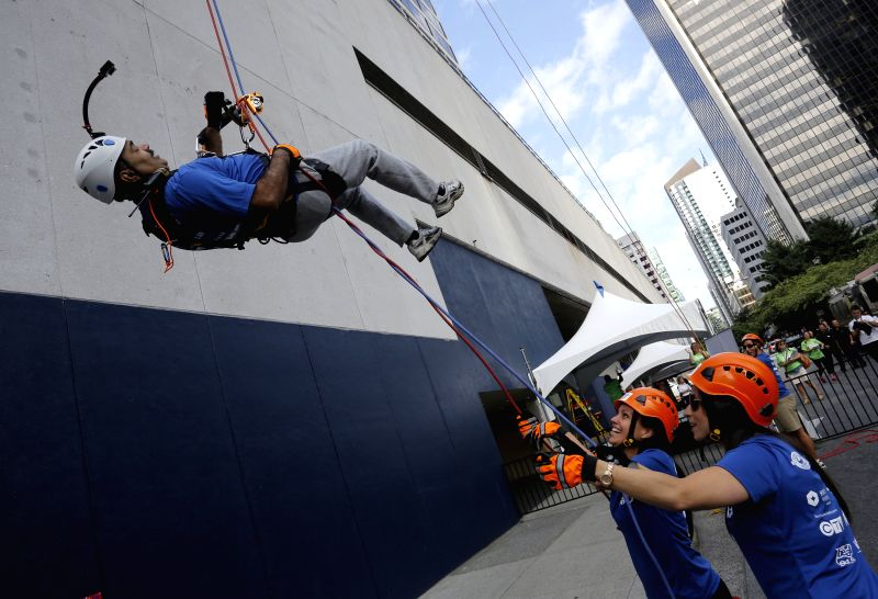VANCOUVER (CANADA), July 23, 2014 A participant lowers down to the ground after rappelling down from the top of the building at Hyatt Regency Hotel in Vancouver, Canada, July 22, 2014. ...