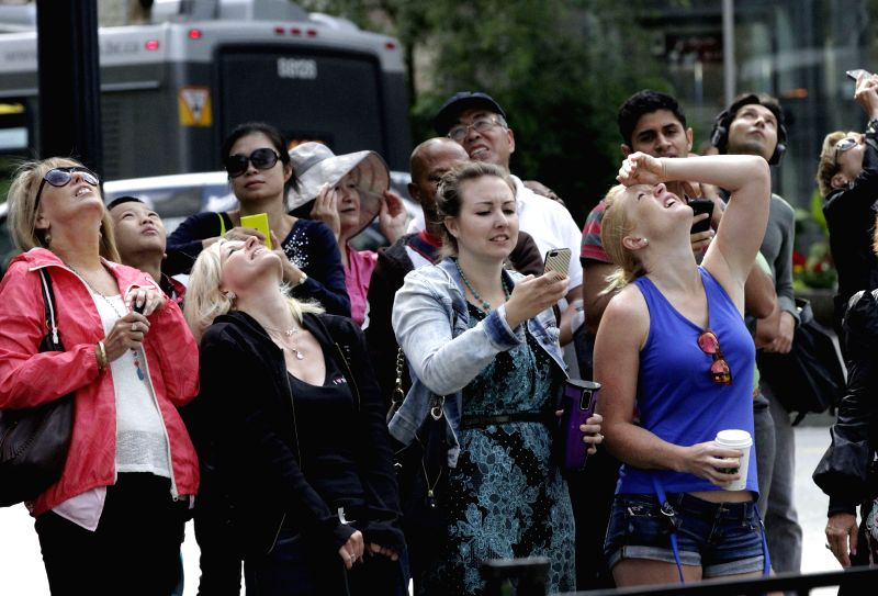 VANCOUVER (CANADA), July 23, 2014 People watch a participant rappelling down the edge of the building at Hyatt Regency Hotel in Vancouver, Canada, July 22, 2014. The Rope for Hope is a ...