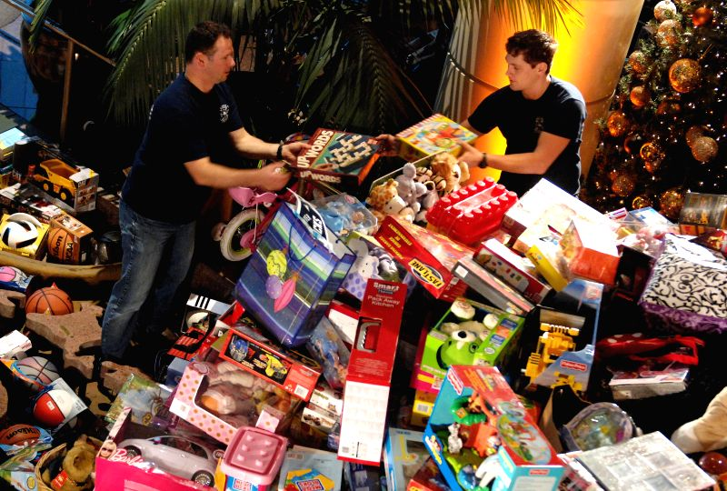 Vancouver (Canada): Vancouver firefighters pile up toys donated by thousands of residents during the 27th annual Pan Pacific Christmas Wish Breakfast in Vancouver, Canada, Dec.11, 2014. More than ...