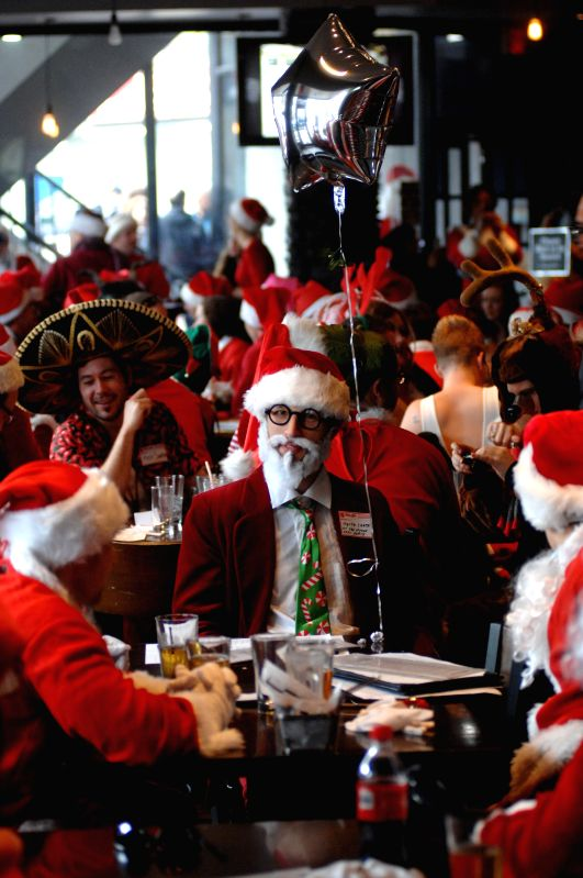 Hundreds of people dressed up in Santa and his helpers' suits take part in the SantaCon 2014 in Vancouver, Canada, on Dec.13, 2014. SantaCon is an annual mass ...