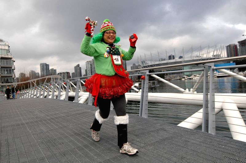 A woman takes part in the Ugly Sweater Run 5K in Vancouver, Canada, on Dec. 13, 2014. Thousands of people around the world took part in the annual event. ...